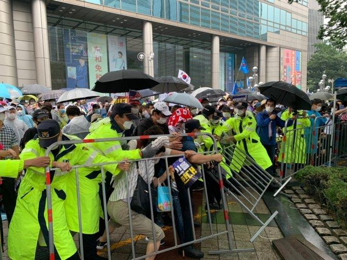 15일 정오 서울 종로구 동화면세점 인근 광화문 일대에서 경찰 통제에 불응한 집회 참가자들이 펜스를 무너뜨리고 있다./사진=이강준 기자