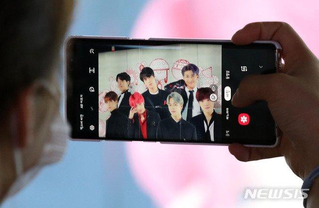 [서울=뉴시스] 고범준 기자 = 그룹 BTS(방탄소년단)의 첫 영어 싱글 '다이너마이트'가 빌보드 싱글차트 1위를 차지한 가운데 1일 오후 서울 중구 롯데면세점에 BTS 광고를 한 시민이 촬영하고 있다. K팝의 역사를 새로 쓴 BTS는 한국 가수 사상 최초로 미국 빌보드 메인 싱글 차트 '핫 100' 정상에 올랐다. 2020.09.01.   bjko@newsis.com