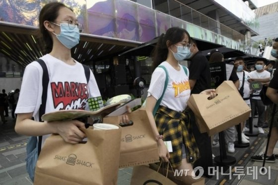 [베이징=AP/뉴시스]12일 중국 베이징에서 첫 '쉐이크쉑'(Shake Shack, 일명 쉑쉑버거) 매장이 개점해 햄버거를 산 손님들이 선물로 받은 기념품을 함께 들고 매장을 나서고 있다. 중국과 미국이 수많은 현안을 놓고 대립하는 상황에서 미국에 본사가 있는 햄버거 체인점이 베이징에 첫 매장을 열었다. 2020.08.12.
