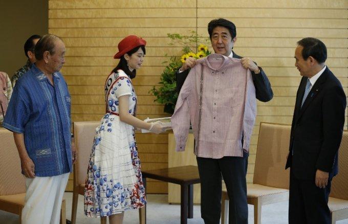 오키나와 전통 의상을 몸에 대보는 아베 신조 일본 총리와 스가 장관(오른쪽 끝). /AFPBBNews=뉴스1