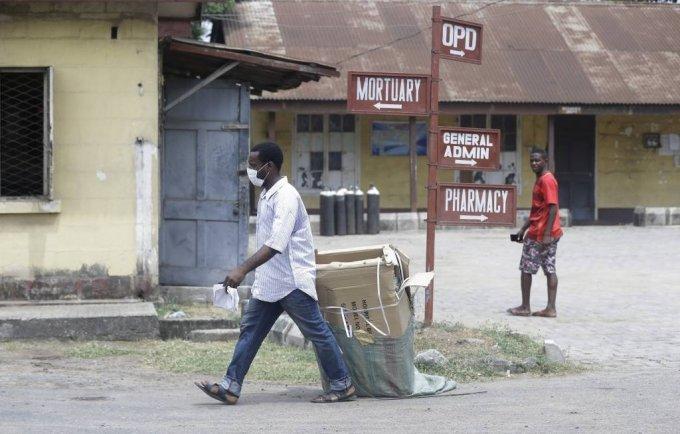 [라고스(나이지리아)=AP/뉴시스]지난 2월 28일(현지시간) 나이지리아 코로나19 확진자가 치료를 받고 있는 라고스의 야바 메인랜드 병원에서 마스크를 쓴 한 남성이 짐을 옮기고 있다. 2020.02.28.