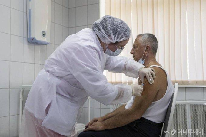 [모스크바=AP/뉴시스]15일(현지시간) 러시아 모스크바에서 한 지원자가 실험용 스푸트니크 V 코로나바이러스 백신을 맞고 있다. 러시아 보건 당국은 위약 조절(placebo-control)이 가능한 4만 명의 무작위 지원자들을 대상으로 이 백신에 대한 시험에 착수했다고 밝혔다. 러시아의 코로나19 누적 확진자 수는 107만3849명, 사망자는 1만8785명으로 집계됐다. 2020.09.16.