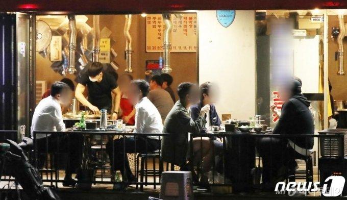 (서울=뉴스1) 민경석 기자 = 14일 오전 0시를 기해 수도권 지역에 내려진 사회적 거리두기 2.5단계가 2단계로 완화됐다. 이날 밤 9시가 넘은 시각, 서울 종로구 일대의 한 술집이 영업을 이어가고 있다.   지난 2주간 영업시간과 방식에 제한을 받았던 식당 및 술집 등을 운영하는 자영업자들은 이날부터 조금이나마 숨통이 트이게 됐다. 2020.9.14/뉴스1