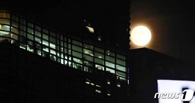 [사진] 불밝힌 사무실 비추는 한가위 보름달