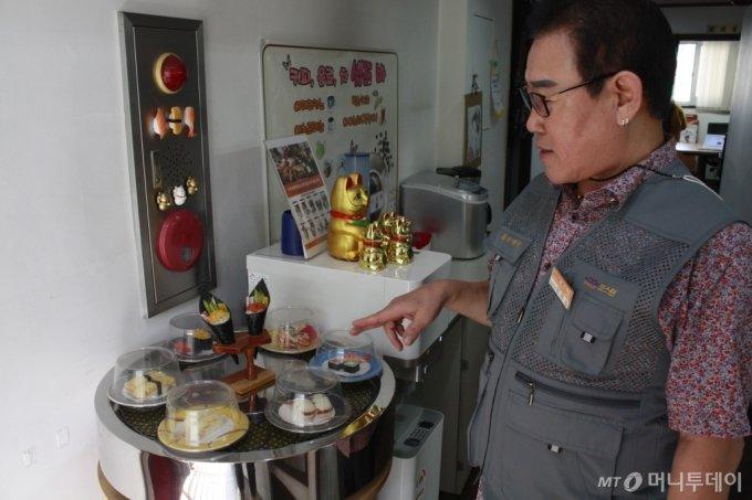 엄천섭 오리온식품기계 대표가 회전초밥 컨베이어에 대해 설명하고 있다 /사진=고석용 기자