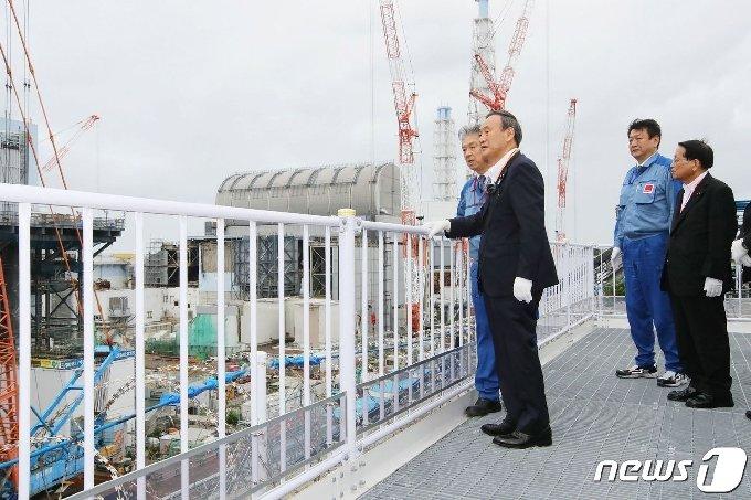 스가 요시히데 일본 총리(오른쪽에서 세번째)가 지난달 26일 후쿠시마 제1원자력발전소를 시찰하고 있다. © AFP=뉴스1