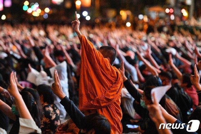 18일 태국 방콕에서 반정부 시위에 참여한 불교 승려가 세 손가락 경례 포즈를 취하고 있다. © AFP=뉴스1