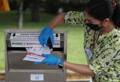 지난 19일(현지시간) 플로리다주 마이애미-데이드 카운티 지역에서 투표 업무 관계자가 우편투표 용지를 우편투표함으로 밀어넣고 있다./사진=AFP