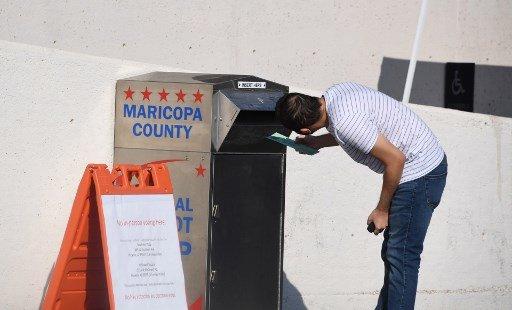 18일(현지시간) 애리조나주 피닉스의 마리코파 카운티에서 한 유권자가 우편투표함에 자신의 투표용지를 넣고 있다. 애리조나주는 미국 대선의 6대 경합주 중 한 곳이다./사진=AFP