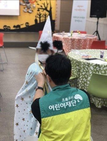 아이에게 마법사 옷을 입혀주는 기자. 사진을 찍어주니, 얌전하던 아이도 무척 좋아했다./사진=초록우산 어린이재단 부산종합사회복지관