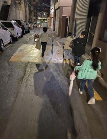 어둑어둑한 골목길을 아이들과 함께. 집까지 안전히 가야지./사진=지나가는 차를 노려보는 남형도 기자