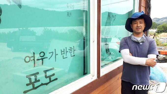 이대겸씨가 자체 브랜드 '여우가 반한 포도' 앞에서 환한 미소를 짓고 있다. © 뉴스1