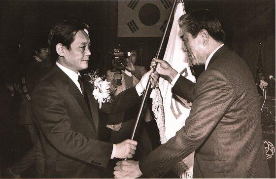 1987년 12월 이건희 삼성 회장이 취임식에서 당시 입사일이 가장 빨랐던 최관식 삼성중공업 사장으로부터 삼성 사기를 받고 있는 모습.