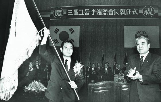 1987년 12월 이건희 삼성 회장이 취임식에서 당시 입사일이 가장 빨랐던 최관식 삼성중공업 사장으로부터 삼성 사기를 받아든 이건희 회장(왼쪽) 모습.
