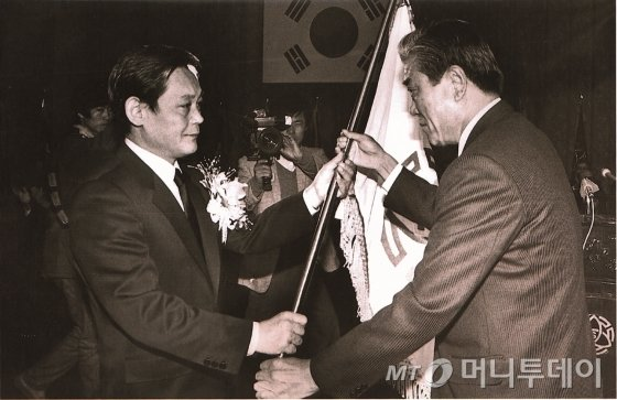 1987년 12월 이건희 삼성 회장이 취임식에서 당시 입사일이 가장 빨랐던 최관식 삼성중공업 사장으로부터 삼성 사기를 받고 있다. /사진제공=삼성전자