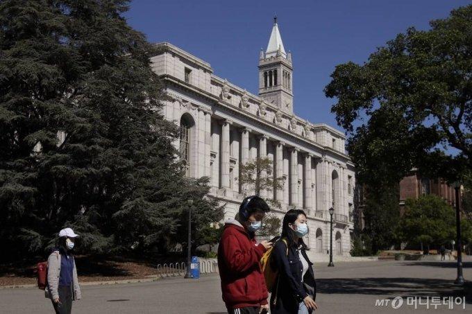 [버클리=AP/뉴시스] 미국 캘리포니아 버클리대(UC버클리) 캠퍼스에서 3월 11일 학생 몇몇이 마스크를 쓴 채 코로나 19로 텅빈 교정을 걷고 있다. 2020.05.22.