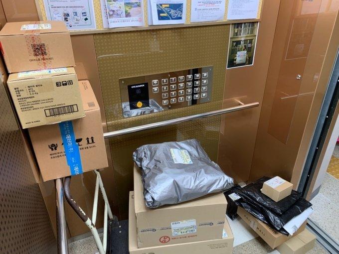 22일 오전 11시쯤 충청남도 서산시의 한 아파트 단지내 엘리베이터에 택배기사 박모씨가 택배 물건을 적재해둔 모습./사진=이강준 기자