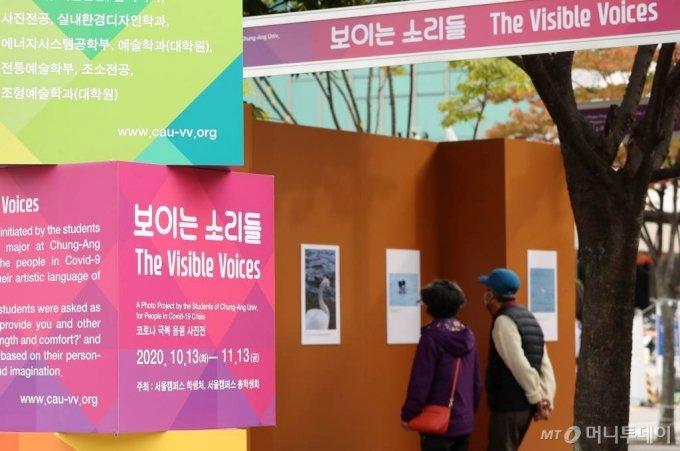 지난달 13일 오후 서울 동작구 중앙대학교 영신관 앞에서 개최된 '코로나19' 극복 응원 사진전을 찾은 시민들이 전시 관람을 하고 있다. / 사진=김휘선 기자 hwijpg@