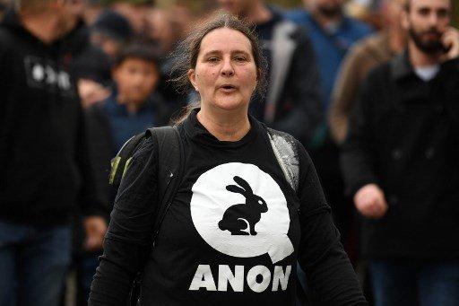 '큐아논'이라고 적힌 티셔츠를 입고 있는 여성/사진=AFP