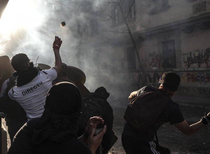 """18일(현지시간) 칠레 수도 산티아고에서 반정부 시위대가 경찰과 대치하며 돌을 던지고 있다. 현지 언론은 지금까지 시위로 22명이 숨졌고 2000명 이상이 다쳤으며 이 중 230여 명이 경찰이 쏜 고무탄에 맞아 실명했다고 전했다. 세바스티안 피녜라 대통령은 시위대의 사회적 요구에 대해 지나치게 강경한 진압과 무력 사용을 시인했으며 """"폭력진압 행위는 처벌받게 하겠다""""라고 약속했다. 2019.11.19./사진=[산티아고(칠레)=AP/뉴시스]"""