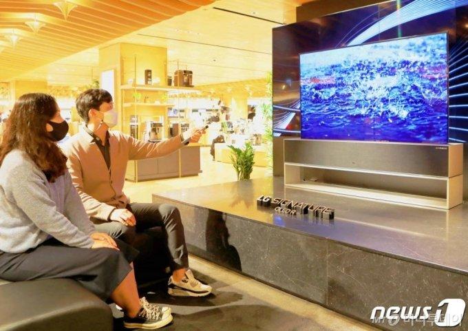롯데백화점이 롤러블 TV 'LG 시그니처 올레드 R'을 직접 체험해 볼 수 있도록 서울 중구 소공동 본점 8층에 프리미엄 팝업 매장을 마련했다. 지난 15일 매장을 찾은 고객들이 'LG시그니처 올레드 R'을 시연해보고 있다.  /사진=뉴스1