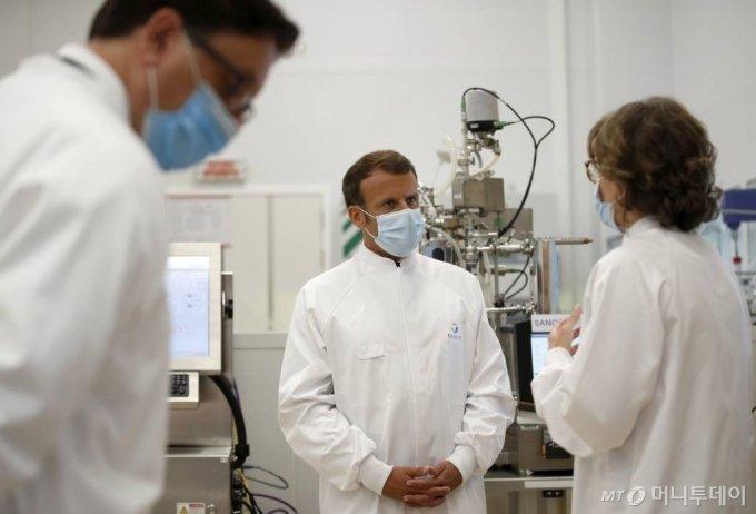 [리옹=AP/뉴시스]에마뉘엘 마크롱(가운데) 프랑스 대통령이 16일(현지시간) 프랑스 중부 리옹 인근 마시 레뚜알 소재 제약회사 사노피파스퇴르 연구소를 방문해 둘러보며 얘기하고 있다. 마크롱 대통령의 이번 방문은 다국적 제약사인 아스트라제네카가 이번 주말 프랑스를 포함한 EU 국가에 4억 명분의 백신을 공급하는 계약을 발표한 후에 이뤄졌다. 2020.06.16.