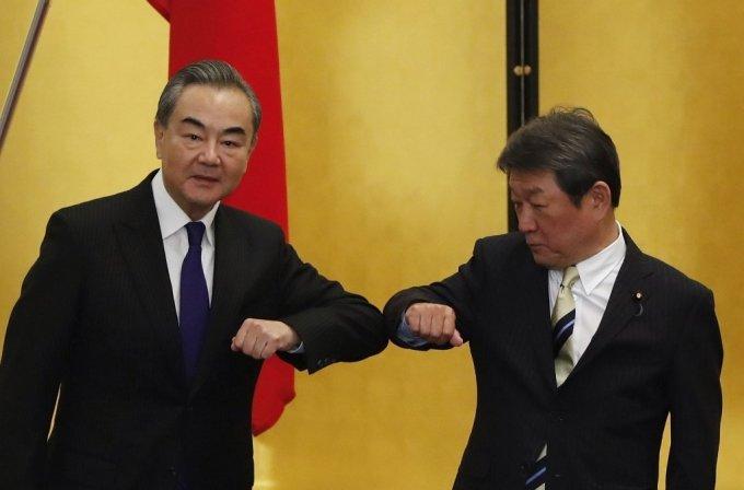 왕이 중국 국무위원 겸 외교부장이 24일 일본 도쿄에서 모테기 도시미쓰 일본 외무상과 회담을 갖기 전 팔꿈치인사를 하고 있다. /사진=AFP