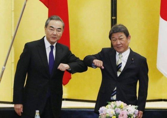 [도쿄=AP/뉴시스]왕이(왼쪽) 중국 외교부장이 24일 일본 도쿄에서 모테기 도시미쓰 일본 외무상과 만나 팔꿈치 인사를 하고 있다. 왕이 부장은 모테기 장관과 만나 중일 관계의 안정적 구축과 코로나19로 피해를 본 경제를 되살리는 방안 등을 논의한 것으로 알려졌다. 2020.11.24.