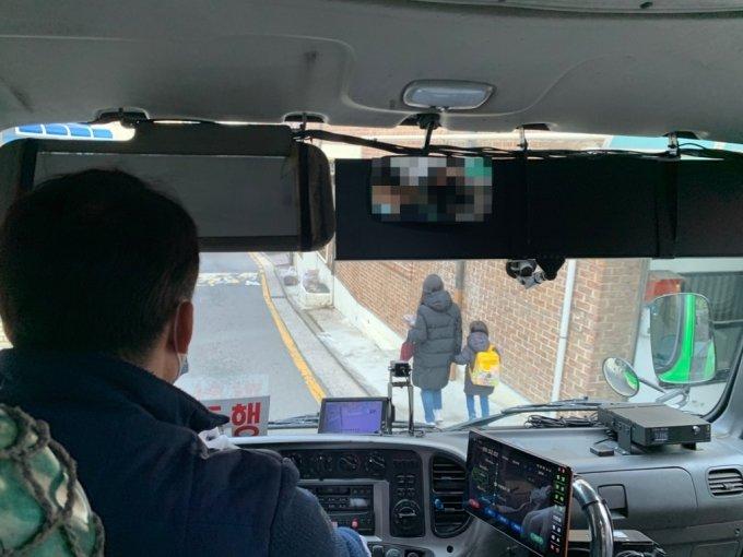 24일 오전 10시쯤 서울 종로구 부암동 부근 한 경사로에서 마을버스가 보호자의 손을 잡고 보행 중인 어린이를 피해서 지나가는 모습/사진=이강준 기자