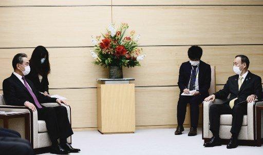 스가 요시히데 일본 총리(오른쪽)가 25일 오후 방일중인 왕이 중국 외교담당 국무위원 겸 외교부장을 도쿄 총리관저에서 접견했다./사진=AFP