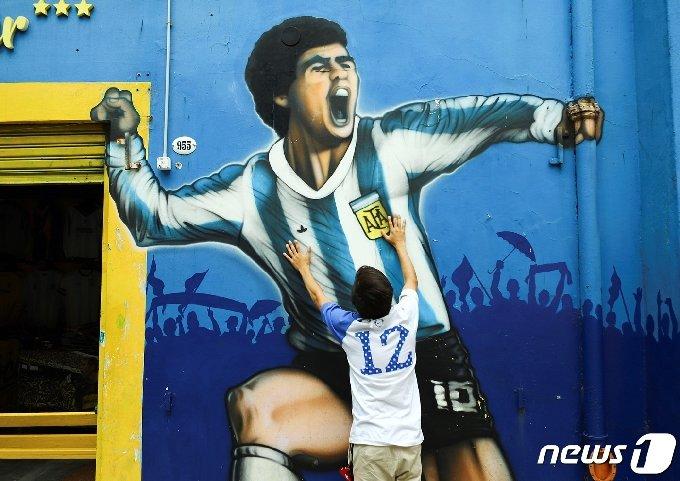 25일(현지시간) 아르헨티나 부에노스아이레스의 알베르토 J. 아르만도 '라 봄보네라' 경기장 밖에서 축구 전설 디에고 마라도나의 죽음을 애도하고 있다. © 로이터=뉴스1 © News1 이동원 기자