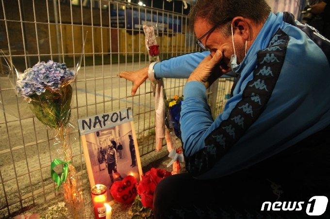 25일(현지시간) 이탈리아 나폴리에 있는 산파올로 경기장 밖에서 축구 팬이 향년 60세에 심장마비로 별세한 아르헨티나의 축구 전설 디에고 마라도나를 애도하며 울고 있다. © AFP=뉴스1 © News1 우동명 기자