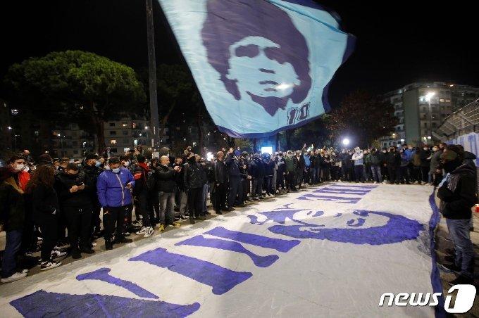25일(현지시간) 이탈리아 나폴리에 있는 산파올로 경기장 밖에서 축구팬들이 아르헨티나의 축구 전설 디에고 마라도나의 별세를 애도하고 있다. 마라도나는 향년 60세의 나이로 숨을 거뒀다. 사인은 심장마비로 알려졌다. © 로이터=뉴스1 © News1 최종일 기자