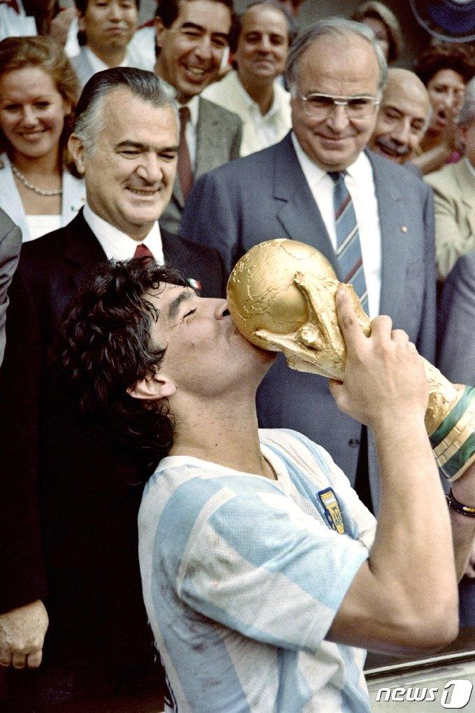 1986년 6월 29일 아르헨티나의 축구팀 주장 디에고 마라도나가 멕시코시티 아즈테카 스타디움에서 열린 서독과의 경기에서 3-2로 승리한 뒤 우승트로피에 입을 마추고 있다. 마라도나는 2020년 11월 25일에 세상을 떠났다. © AFP=뉴스1 © News1 이동원 기자