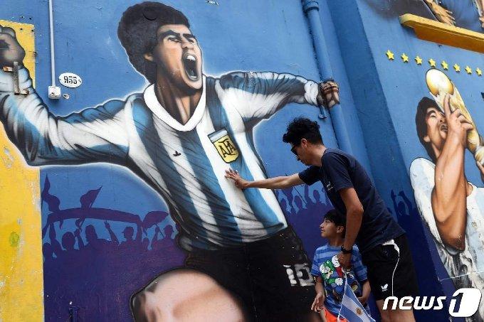 25일(현지시간) 부에노스아이레스 라보카 인근에서 아르헨티나의 축구 전설 디에고 마라도나를 묘사한 벽화 옆에서 한 남자와 아이가 헌화를 하고 있다. © AFP=뉴스1 © News1 이동원 기자