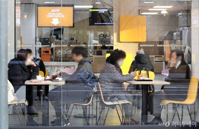 [서울=뉴시스]이윤청 기자 = 수도권 사회적 거리두기 2단계가 시행되면서 카페 내 취식을 금지하고 있는 26일 서울 중구의 한 패스트푸드 음식점에서 시민들이 커피 등 음료를 마시고 있다. 2020.11.26.   radiohead@newsis.com