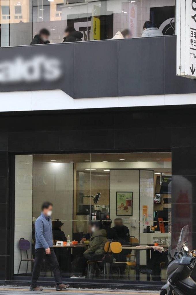 [서울=뉴시스]이윤청 기자 = 수도권 사회적 거리두기 2단계가 시행되면서 카페 내 취식을 금지하고 있는 26일 서울 중구의 한 패스트푸드 음식점에서 시민들이 음료를 마시고 있다. 2020.11.26.   radiohead@newsis.com