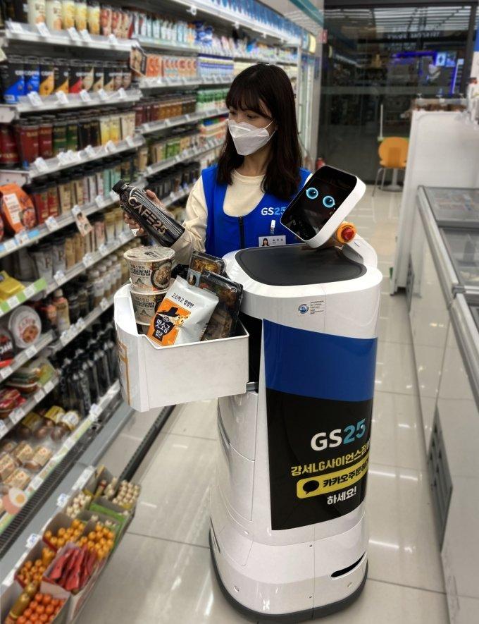 GS25직원이 배달 로봇 딜리오에 주문 받은 상품을 적재하고 있다./사진제공=GS리테일