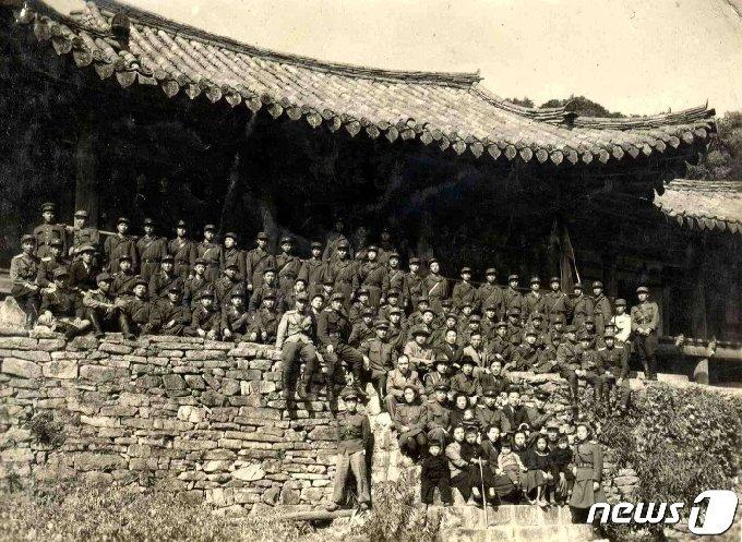 1949년 10월 김일성 수상이 인민군 대원들과 함께 천주사를 방문해 천주루 앞에서 기념촬영하고 있다. 4번째 줄 가운데에 김일성 수상이 앉아 있고, 맨 앞줄에 어린 김정일(왼쪽에서 3번째)의 모습이 보인다. (미디어한국학 제공) 2020.12.12.© 뉴스1