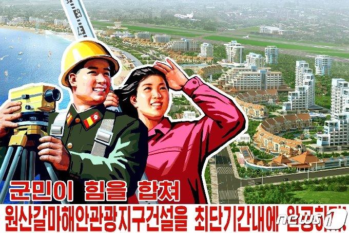 2018년 원산 갈마해안지구의 건설조감도를 배경으로 만든 북한의 선전포스터. 원래 2019년 완공 계획이었으나 여러 차례 완공이 미뤄져 아직까지 준공식을 하지 못하고 있다. (평화경제연구소 제공) 2020.12.19.© 뉴스1