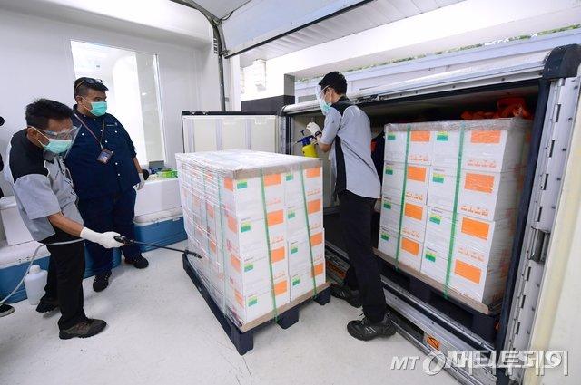 [반둥=AP/뉴시스]7일(현지시간) 인도네시아 반둥에 있는 국영 제약사 바이오파마 관계자들이 이날 도착한 중국 시노백의 코로나19 백신 상자들을 소독하고 있다. 인도네시아 정부는 중국 시노백 바이오테크가 개발한 120만 회 분량의 코로나19 백신이 6일 늦게 인도네시아에 도착했으며 1월 초에 더 많은 백신이 도착할 것이라고 밝혔다. 2020.12.07.