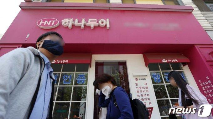 지난 5월 서울 종로구에 위치한 하나투어 대리점 간판을 단 한 소규모 여행사의 불이 꺼진 가운데 시민들이 지나는 모습. /사진=뉴스1