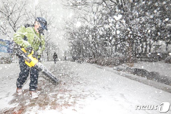 12일 오후 경기도 고양시 호수공원에서 관계자들이 갑자기 내리는 폭설에 제설작업을 하고 있다. 이날 기상청은 낮부터 추위가 풀리며 서울·경기 지방에 눈이 내릴 것으로 예보했다. 2021.1.12/뉴스1 © News1 성동훈 기자