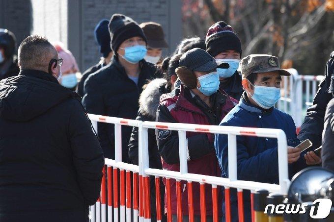 12일 중국 수도 베이징에서 노동자들이 코로나19 백신을 맞기 위해 줄을 서 있다. © AFP=뉴스1