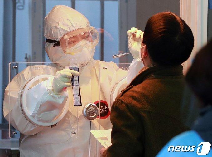 14일 오전 서울역 광장에 마련된 신종 코로나바이러스 감염증(코로나19) 임시선별진료소에서 의료진이 피검사자의 검체를 채취하고 있다. 2021.1.14/뉴스1 © News1 구윤성 기자