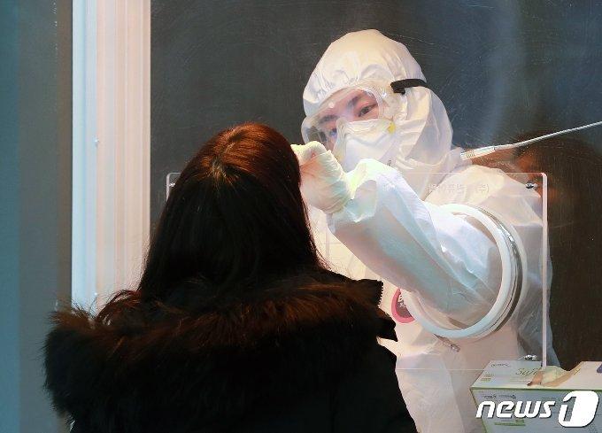 14일 오전 서울역 광장에 마련된 신종 코로나바이러스 감염증(코로나19) 임시선별진료소에서 의료진이 피검사자의 검체를 채취하고 있다. 질병관리청 중앙방역대책본부에 따르면 이날 0시 기준으로 코로나19 신규 확진자는 524명 발생했다. 전날 562명에 비해 38명 감소한 규모다. 지역발생 사례는 496명, 해외유입은 28명이다. 수도권 지역발생 확진자는 317명(경기 162명, 서울 131명, 인천 24명)으로 전체 63.9% 비중을 차지했다. 2021.1.14/뉴스1 © News1 구윤성 기자