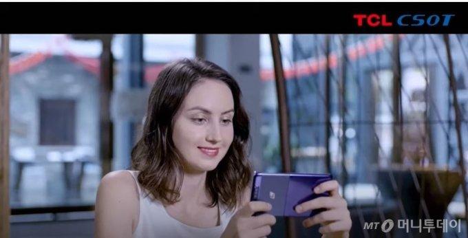 중국 업체 TCL이 공개한 롤러블 폰, 휴대폰을 세로로 세웠을 때는 위로, 가로로 세웠을 때는 옆으로 늘어나는 롤러블 폰이다. 실제 제품은 공개하지 않고 동영상 이미지만 공개됐다./사진제공=TCL 동영상 캡쳐.