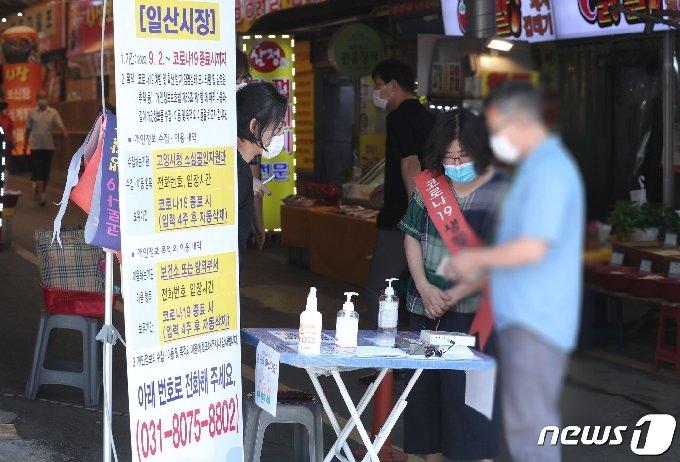 고양시 일산시장 입구에서 시장 방문 시민들이 안심콜 출입관리 시스템을 안내받고 있다. (고양시청 제공)© 뉴스1