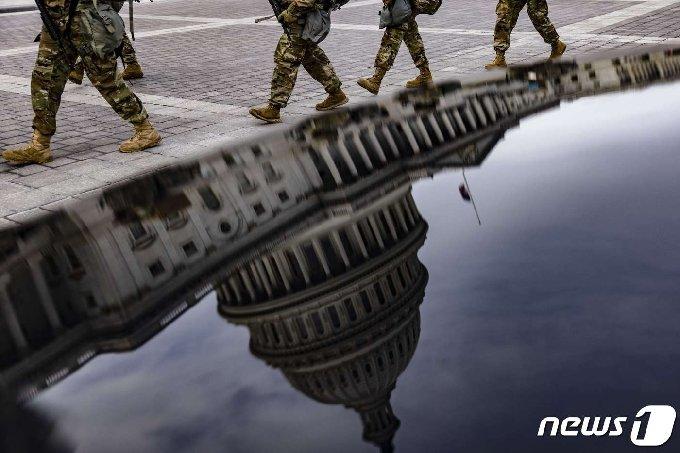 16일(현지시간) 미국 버지니아 주방위군 병사들이 워싱턴DC 의사당 동쪽을 가로질러 감시 초소로 가고 있다. © AFP=뉴스1