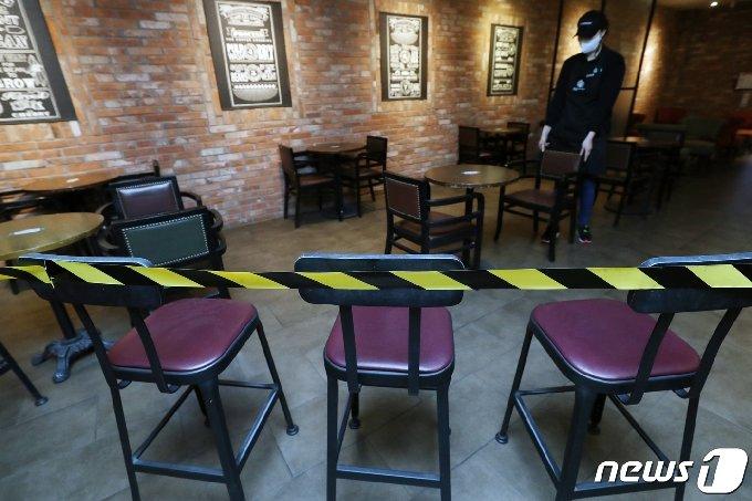 18일부터 카페 매장 내 취식이 가능해진다. 정부는 지난 16일 발표한 신종 코로나바이러스 감염증(코로나19) '사회적 거리두기' 조정안을 통해 전국 카페에서 오후 9시까지 매장 내 취식이 가능하다고 밝혔다. 17일 서울의 한 커피 전문점에서 직원이 매장 한 쪽에 치워놨던 탁자와 의자를 다시 제자리로 옮겨 정리하고 있다. 2021.1.17 /뉴스1 © News1 민경석 기자